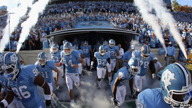 University of North Carolina football players run onto the field in 2010.