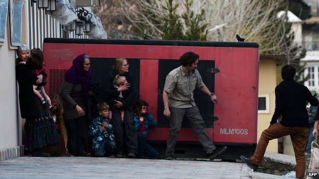 Foreigners take refuge behind a generator after they were evacuated from a guesthouses during an attack by Taliban gunmen (28 March 2014)
