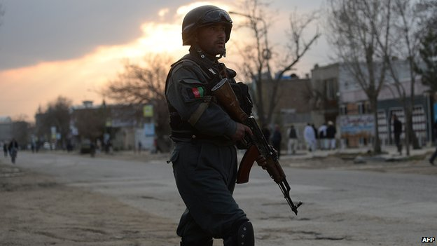An Afghan policeman stands guard near a guesthouse attack by Taliban fighters in Kabul on March 28, 2014