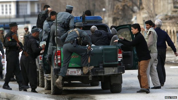 Afghan policeman evacuate foreigners from a guest house, the site of an attack, in Kabul (28 March 2014)