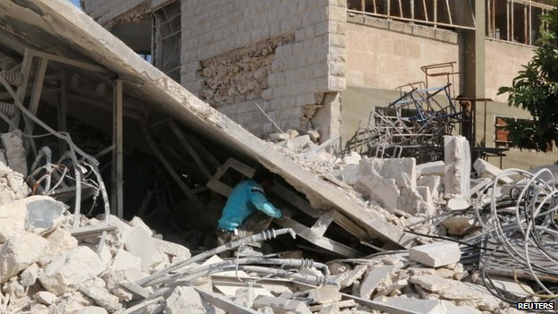 A man searches among rubble at a site hit by what activists said were barrel bombs dropped by forces loyal to President Bashar al-Assad in Karam