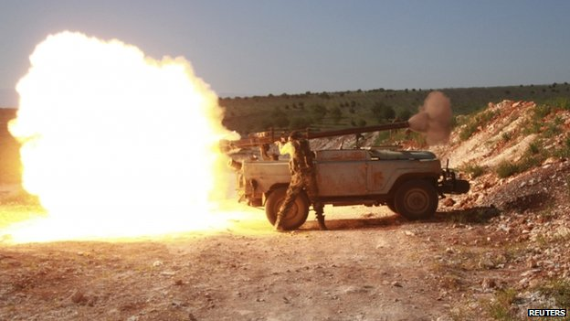 Free Syrian Army fighters fire towards forces loyal to Syria's President Bashar al-Assad in the north Hama countryside