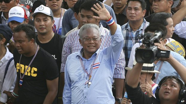 Thai anti-government protest leader Suthep Thaugsuban, centre, waves to supporters while making his way on the street during a mass rally in Bangkok, Thailand on 29 March 2014.