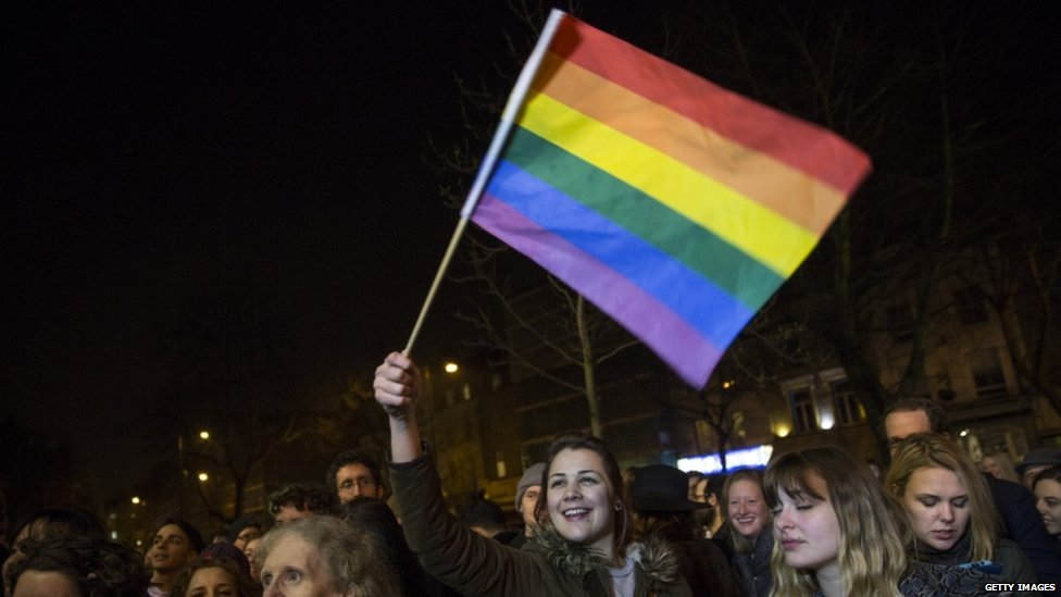 A gay marriage supporter waves a rainbow flag