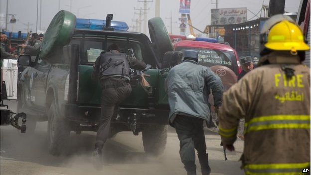 Afghan policemen run to jump on their car as Taliban militants attack the main Afghan election commission's headquarters