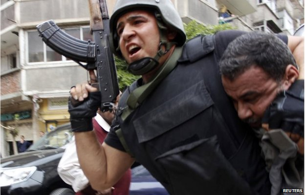 A member of the security forces detains a protester during clashes with supporters of Mohamed Morsi in Alexandria