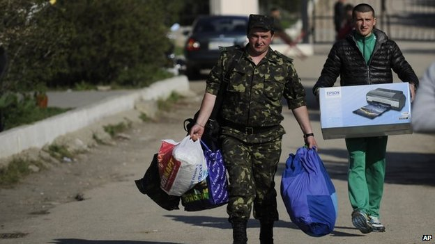 Ukrainian servicemen carry their belongings as they leave the Belbek airbase near Sevastopol