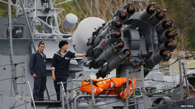 Sailors stand next to a weapons system onboard a Russian Navy vessel anchored at a navy base in the Ukrainian Black Sea port of Sevastopol