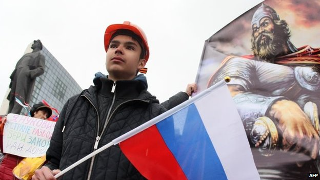 A Pro-Russian activists holds a Russian flag during a rally in Donetsk