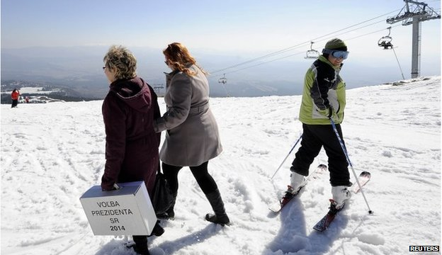 Electoral committee members walk through the snow at a ski resort with a mobile ballot box after voters from an alpine chalet cast their votes