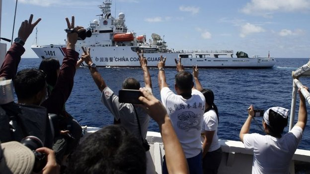 Philippine Marines and a local television reporter (L) gesture towards a Chinese Coast Guard vessel in the South China Sea March 29,