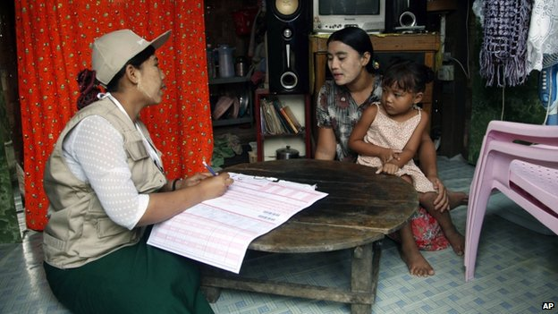 A Myanmar census enumerator asks questions to a housewife while collecting information in Dala township on 30 March 2014, in Yangon, Myanmar