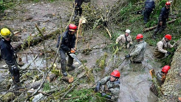 Personnel from the Washington National Guard join civilian workers in cutting operations following a deadly mudslide in Oso, Washingtonon 28  March 2014.