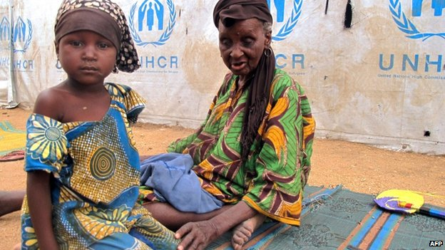 A little girl and an elderly woman sit by a UNHCR tent in the refugee camp of Minawao, on the border of Nigeria at the extreme north of Cameroon, on 29 March 2014.