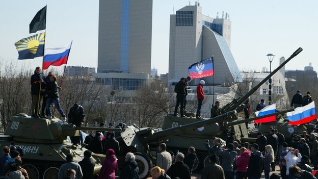 Pro-Russian demonstrators stand atop of Soviet era tanks holding Russian national flags at a World World 2 museum in Donetsk, on 30 March 2014
