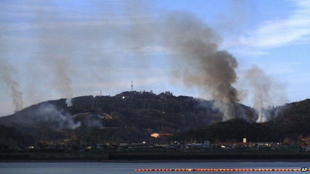 Smoke billows up from Yeonpyeong island near the border against North Korea, in South Korea on 23 Nov 2010