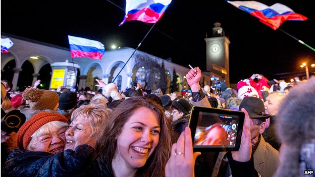 People celebrate the transition to Moscow time near a city clock tower at a railway station in Simferopol (March 30, 2014)