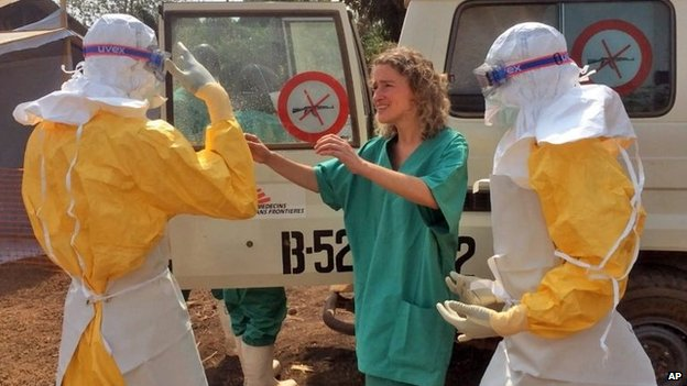 In this photo provide by MSF, Medecins Sans Frontieres (Doctors without Borders), taken on Friday, March 28, 2014, healthcare workers from the organisation, react, as they prepare isolation and treatment areas for their Ebola, hemorrhagic fever operations, in Gueckedou, Guinea.