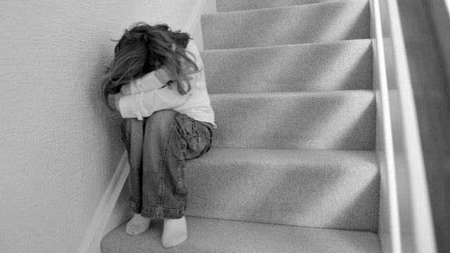 Young girl sits on a staircase and covers her face