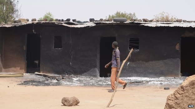 A villager walks past razed homes in Mainok, outside Maiduguri, Borno State, Nigeria, on March 6, 2014.