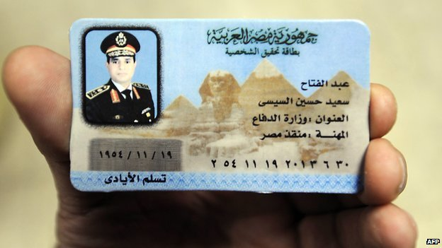 An Egyptian man displays a souvenir fake ID card depicting Egypt's ex-Field Marshal Abdul Fattah al-Sisi, on sale in Cairo on 28 January 2014