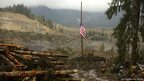 A flag flies at half-mast on the slope of the massive mudslide that struck Oso in the background near Darrington, Washington