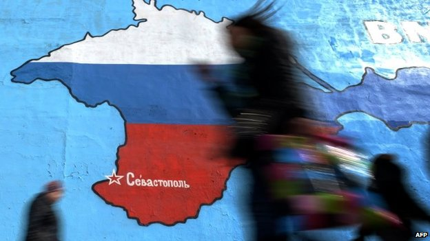 People walk past a mural in Moscow showing a map of Crimea bearing the colours of the Russian flag (31 March 2014)