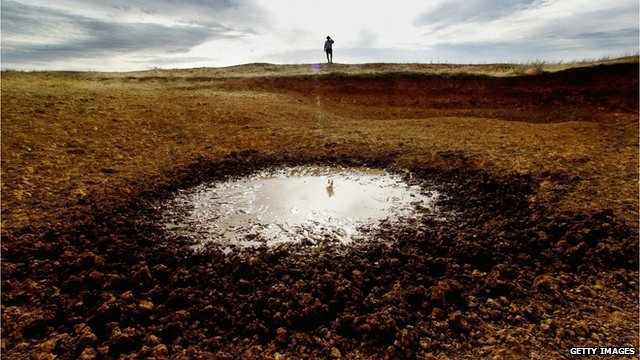 An Australian farmer inspects a dried up dam on his farm