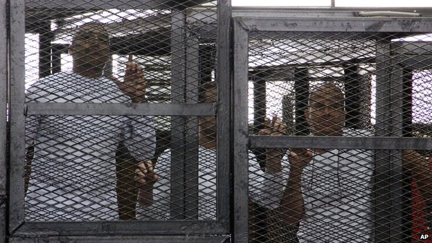 Al-Jazeera English bureau chief Mohammed Fahmy, left, producer Baher Mohamed, centre, and correspondent Peter Greste, right, appear in a defendant's cage in a courtroom along with several other defendants during their trial on terror charges, in Cairo, Egypt, on 31 March 2014.