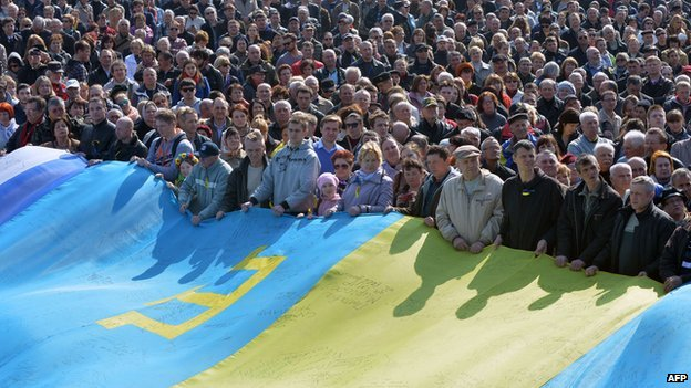 People hold a huge flag, a combination of a Ukrainian, Crimean and Tatar flags, on Independence Square in Kiev on 23 March 2014.