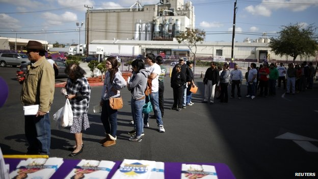 People wait in line to sign up for health insurance at an enrolment event in Commerce, California, on 31 March 2014.