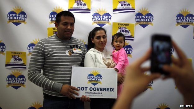 Enrique Gonzalez, 22, Janet Regalado, 21, and their nine-month-old daughter pose for a photo after signing up for health insurance in California on 31 March 2014.