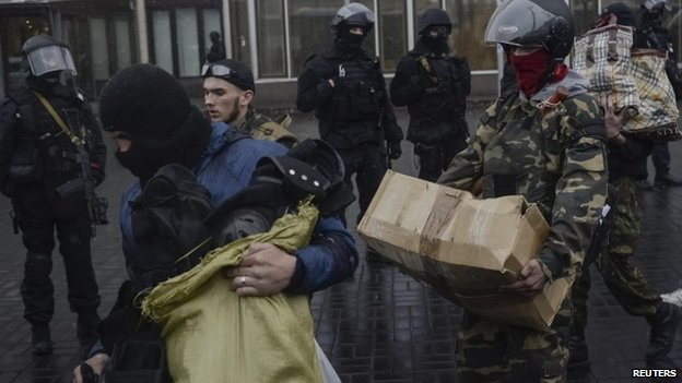 Members of the Ukrainian radical group Right Sector leave their headquarters in Dnipro Hotel in Kiev as police special forces stand guard. Photo: 1 April 2014