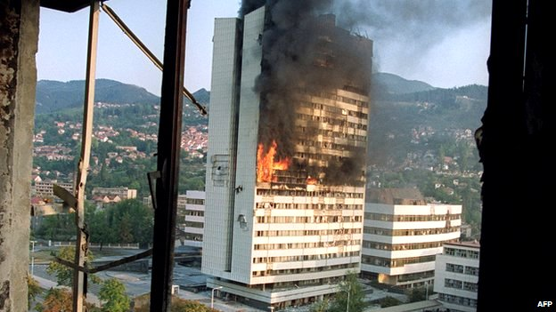 Parliament building aflame in Sarajevo after being struck by a shell