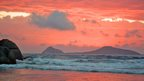 A salmon pink sky with a couple of clouds overlooks an island in the sea.