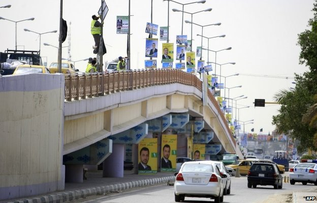 Workers hang electoral posters from lampposts in Baghdad (1 April 2014)