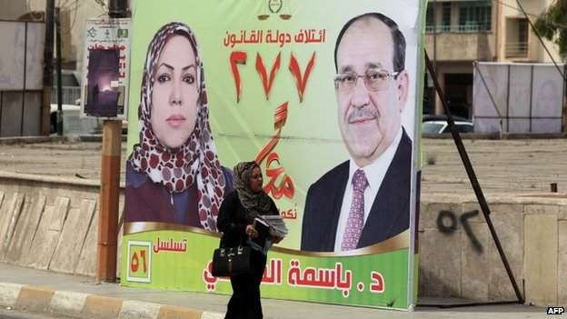 A woman walks past an election poster in Baghdad featuring a female candidate and Prime Minister Nouri Maliki (1 April 2014)