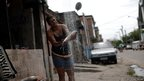A woman cleans a fish  on the streets of the Mare slums complex, Rio de Janeiro