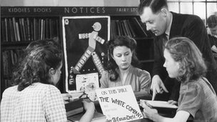 School children look at books with a librarian in 1946