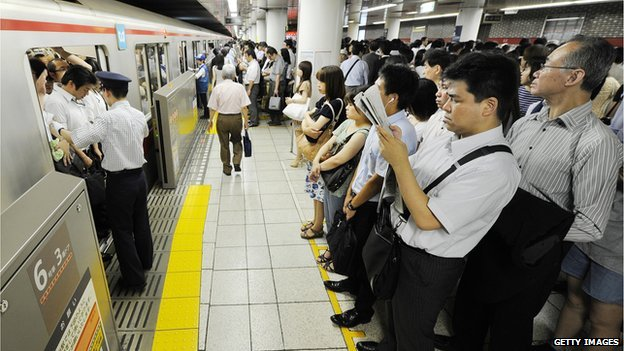 People wait to get on a Tokyo subway train