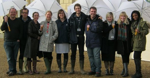 BBC Berkshire staff pose outside their Cavesham offices under umbrellas