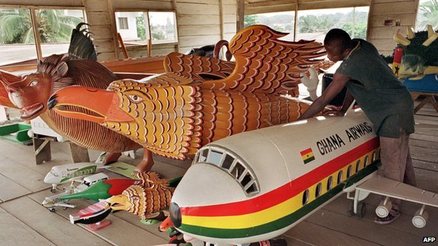 A man prepares coffins representing a plane and animals in Accra on 12 December 2000
