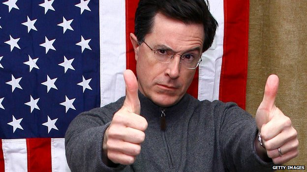 Stephen Colbert gives a thumbs-up in front of a US flag