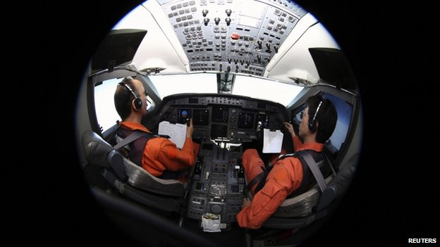 Pilots sit in the cockpit of the Japan Coast Guard Gulfstream V aircraft as it flies over the southern Indian Ocean looking for debris from missing Malaysian Airlines flight MH370, 1 April 2014