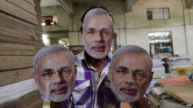 An Indian worker poses with masks bearing the face of BJP PM candidate Narendra Modi at a printing press near Ahmedabad on March 31, 2014