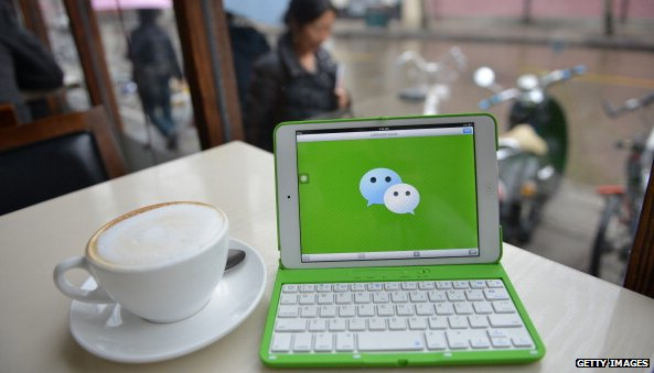 WeChat logo on laptop next to coffee cup