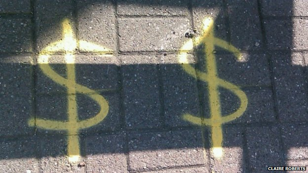 dollar signs on the road