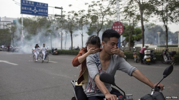 Residents cover their faces as they ride a motorcycle along a street after tear gas was released by police to disperse a protest against a chemical plant project in Maoming, Guangdong province, on 31 March 2014