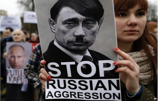 "Demonstrator outside the Russian embassy in Vilnius holds up a sign saying ""Stop Russian aggression"""