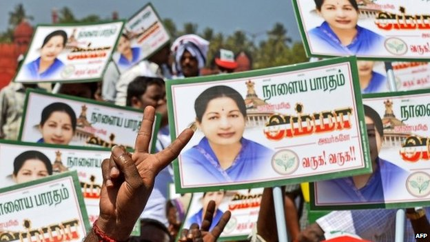 Supporters of J Jayalalithaa wave placards ahead of a public meeting in Pondicherry on March 27, 2014